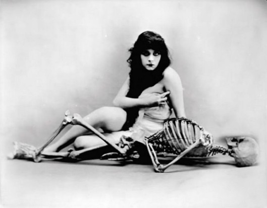 theda bara posing with a skeleton